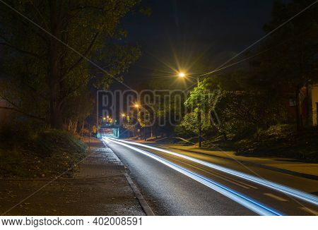 Asphalt Road Running Under The Railway Viaduct.\nasphalt Road At Night. It Is A Two-way Road, Lit By