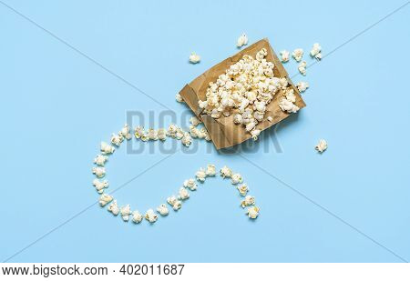 Popcorn Exploding In Paper Bag With Fuse, Isolated On Blue Background. Flat Lay With Popcorn Bag, Ho