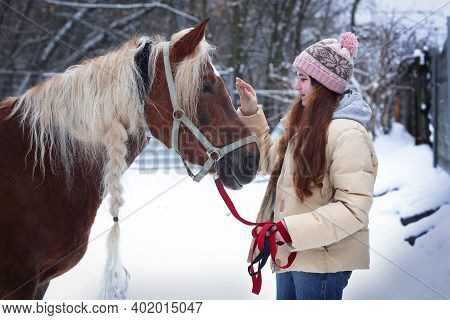 Girl With Long Brown Hair And Chestnut Horse With Plaited Mane Close Up Portrait On Winter Snowy Bac