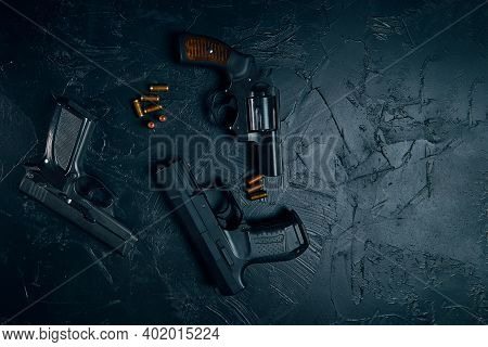 Top View Of Pistols And Copper Bullets On Black Concrete Table. Vintage Revolver With A Drum. 9mm Ha