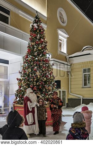 Yekaterinburg, Russia - January 4, 2021: Little Girl Recites A Poem To Santa Claus Near The Christma