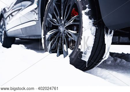 Car With Winter Tires On Light-alloy Wheels On Snow At Shallow Depth Of Field