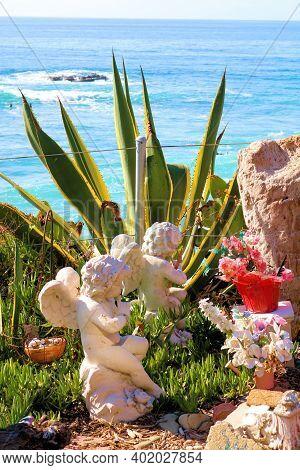 January 4, 2020 In Laguna Beach, Ca:  Angel Sculptures Besides Plants Overlooking The Ocean Taken At