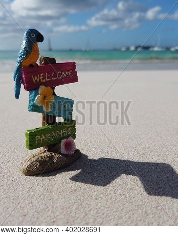 A Miniature Welcome To Paradise Sign On A Tropical Beach