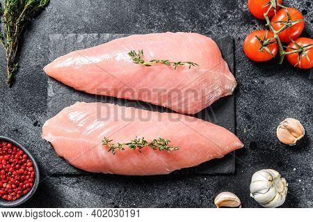 Raw Turkey Steaks. Breast Fillet. Black Background. Top View.