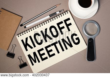 Kickoff Meeting, Text On Notepad Sheet On Brown Background Near Magnifier And Coffee Cup