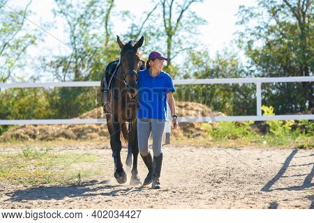 Girl After Everyday Equestrian Training Goes Across The Field With A Horse