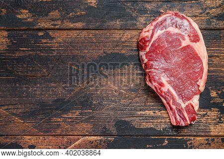 Raw Cowboy Or Rib Eye Steak On The Bone. Marble Beef Meat Ribeye. Dark Wooden Background. Top View.