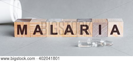 Malaria Is A Word Written In Black Letters On Wooden Cubes, Grey Background. Malaria Text On Wooden