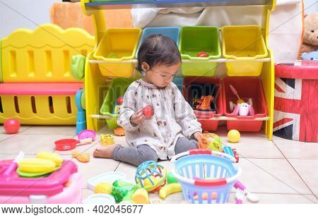 Cute Asian Toddler Girl Child Sitting On Floor Having Fun Playing Alone In Playroom At Home, Little