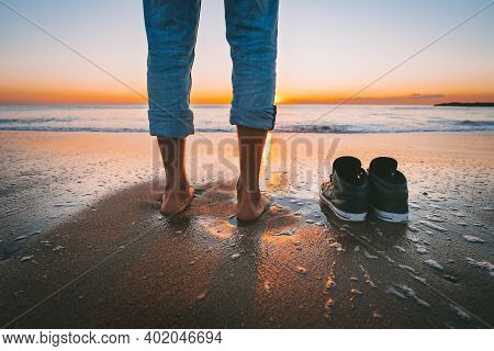 Closeup Of Barefoot Man Walking On The Summer Beach At Sunset. Man Take Off His Shoes For Walk In Th
