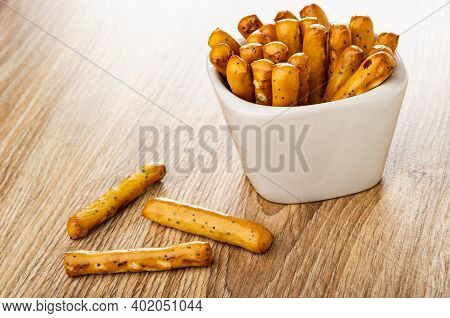 Breadsticks With Poppy In Glass White Bowl, Breadsticks On Brown Wooden Table