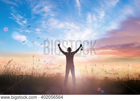 Win Concept: Silhouette Champion Hand Holding Number 1 Of Medal Against Meadow Sunset Background