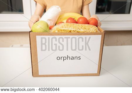 A Young Woman Volunteer With A Box Of Food Products For Orphans In Orphanages
