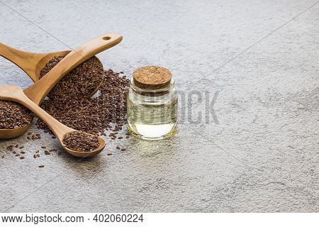 A Jar Of Linseed Oil Flax Seeds In A Wooden Spoon On A Concrete Background, A Dietary Cereal Ingredi
