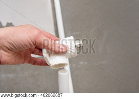 Connector Of Plumbing Pipes In The Hand. Male Threaded Pipe Fitting On Dark Gray Cement Background,