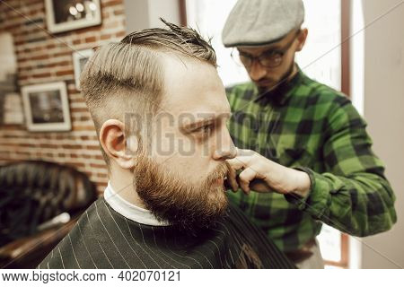 Young Bearded Man Getting Haircut While Sitting In Chair At Barbershop. The Hairdresser Cuts And Com