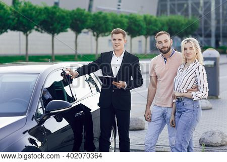 A Young Car Dealer In A Business Suit Shows Buyers A New Car. Young Couple, Man And Woman, Buy A Car