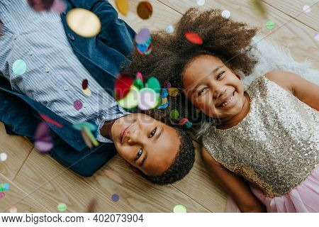 Siblings Lying On The Floor Under Confetti
