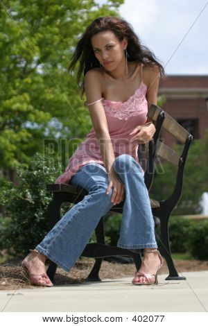 Beautiful, Young Girl In A Provocative Pose Sitting On A Bench