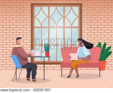 Business People Man And Woman Are Sitting At The Table Typing On Laptops And Talking In Modern Inter