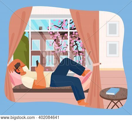 Young Man Lying On Windowsill At Home Serfing Internet With Phone. Male Character Resting In Room Ne