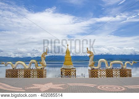 Naga Statue Or Phayanak With A Bright Sky, Clouds, Mountains Background And Freshwater Lake (kwan Ph