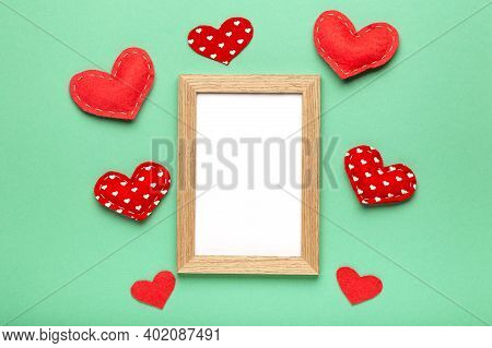 Love Frame With Hearts On Green Pastel Background Top View Copy Space. Valentine's Day Background