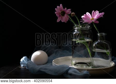 Still Life With Delicate Flowers Of Daisies With Rose Petals On A Dark Wooden Background With A Kitc