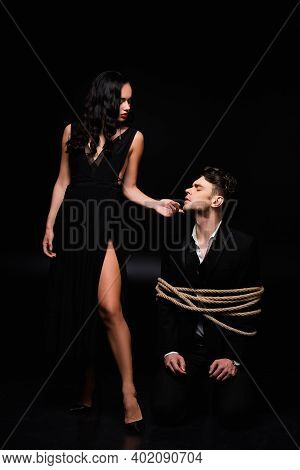 Full Length Of Dominant Woman In Dress Standing And Touching Face Of Tied Submissive Man In Suit On