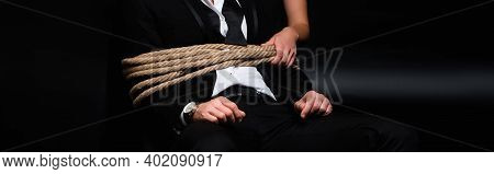 Cropped View Of Dominant Woman Holding Rope On Tied Submissive Man Sitting On Black, Banner