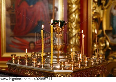 Several Burning Candles Against The Background Of The Church Altar.