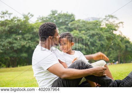Happy African American Father While Hug And Carry His Son, Dad Was Kissing His Son In The Park, Joyf