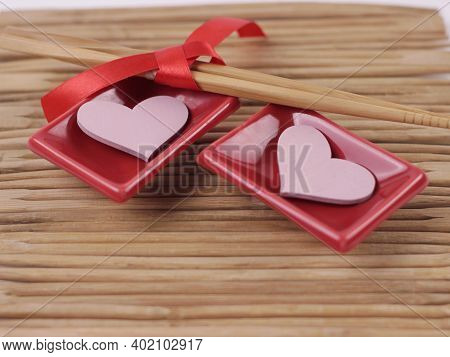 Valentine's Day Concept. Dinner Party Table Setting. Set Of Sushi, Pink Hearts Closeup On Mat Of Cho