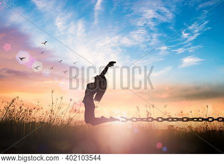 New Normal Concept: Silhouette Of A Girl Jumping And Broken Chains At Autumn Sunset Meadow With Her
