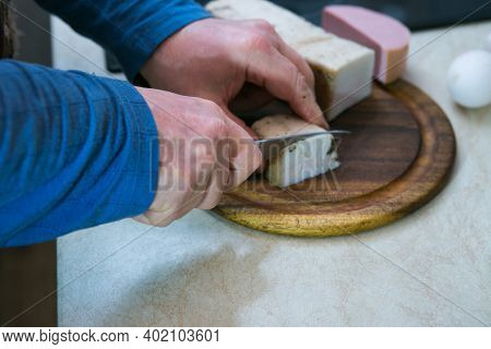 The Process Of Making An Omelet With Lard And Sausage. The Man Prepares Two Portions. A Man Cuts Lar