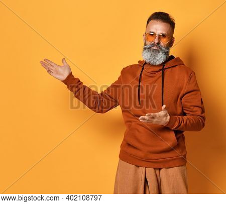 Serious Brutal Handsome Grey-haired Bearded Man Wearing Casual Sportswear Pointing To Left Looking A