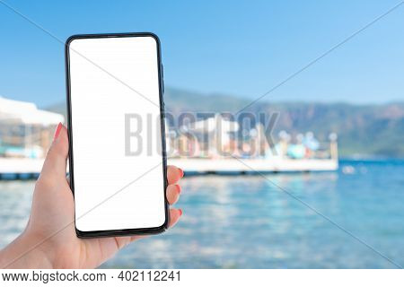 Mockup Image Of A Woman Hand Holding Cell Smart Mobile Phone With Blank Desktop Screen By The Sea An