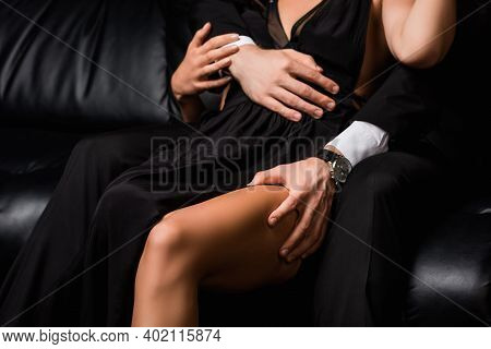 Cropped View Of Man In Suit Seducing Young Woman While Sitting On Black Sofa