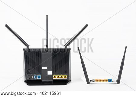 Rear View Of  Two Wi-fi  Routers, Wireless Devices With Two  And Three Antennas.  Black Router Has