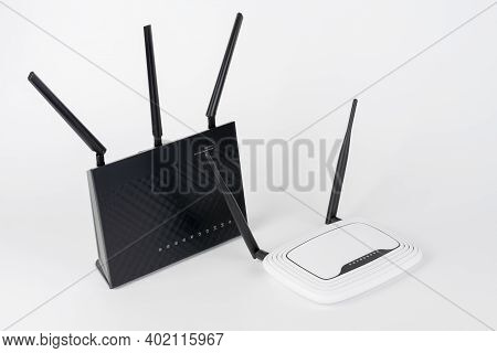 Two Wi-fi  Routers, Wireless Devices With Two And Three Antennas.  Black Router Has Five Gigabit Eth