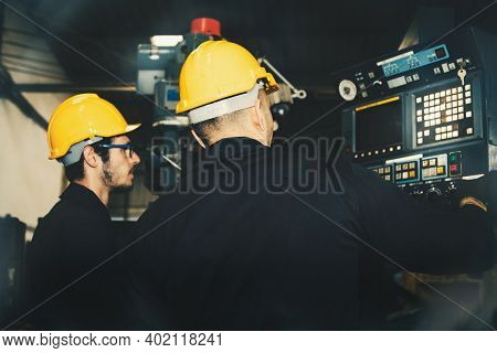 Engineering Team Of Male Electricians In An Industrial Factory Uses A Laptop Computer To Inspect The