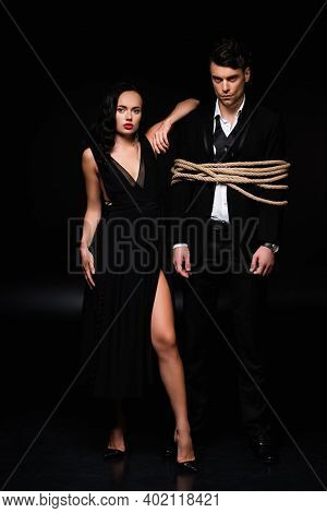 Full Length Of Dominant Woman In Dress Standing With Tied Submissive Man In Suit On Black