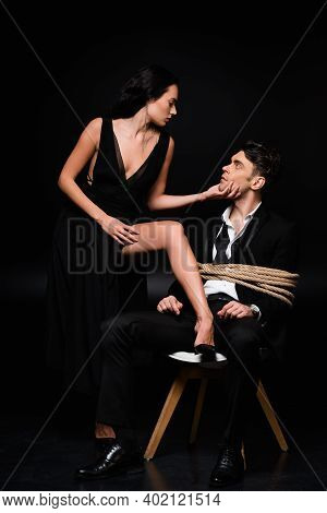 Full Length Of Seductive Woman In Dress Touching Face Of Tied Submissive Man Sitting On Chair On Bla