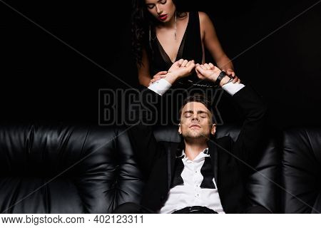 Dominant Woman In Dress Looking At Submissive Handcuffed Man Isolated On Black