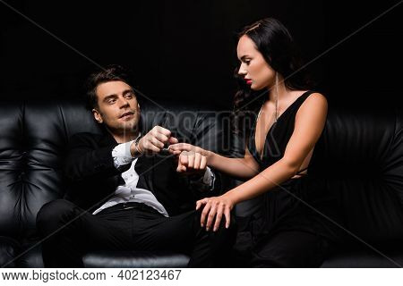 Sexy Woman In Dress Pulling Handcuffs On Submissive Man Isolated On Black