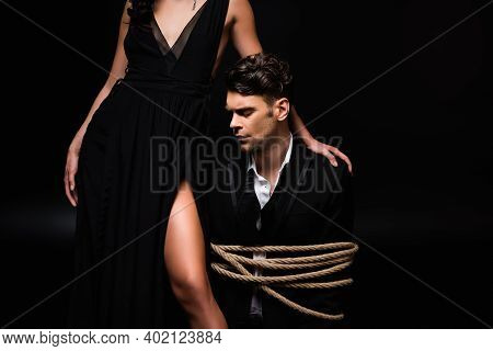 Woman In Dress Standing With Tied Submissive Man In Suit On Black