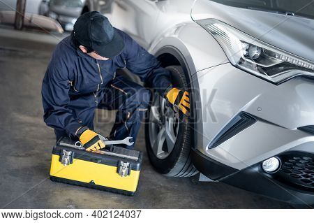 Asian Auto Mechanic With Tool Box And Wrench Checking Car Wheel And Tire In Auto Service Garage. Mec