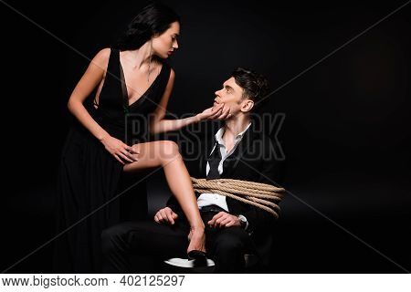 Seductive Woman In Dress Touching Face Of Tied Submissive Man Sitting On Chair On Black