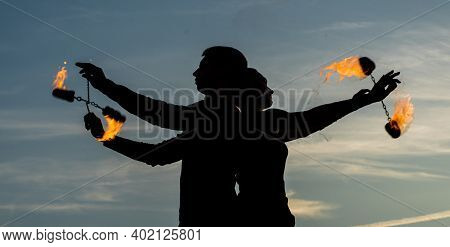 Couple In Love Perform Fire Poi Spinning In Evening Shades On Idyllic Sky Outdoors, Burning